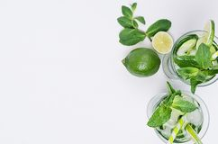 Border of cold drink with ice cubes, slices lime, cucumber, straw, twigs mint with copy space on white wood board, top view. Royalty Free Stock Image