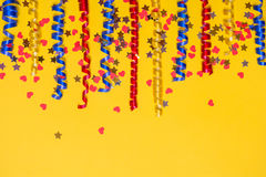 Border of colored festive ribbons and confetti on a yellow background. Gift scenery. Royalty Free Stock Photos