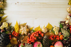 Border from colorful autumn leaves, mushrooms, rose hips, rowanberry, apples, nuts, cones and cookies on the wooden background. Fall background Royalty Free Stock Photos