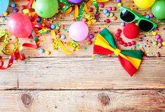 Border of colorful party accessories. Balloons, candy and confetti for a Mardi gras or carnival on rustic wood with copy space