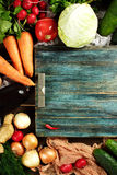 Border composition made with fresh vegetables. On wooden rustic table with blue vintage tray. Top view, space for text. Eggplants, cabbage, carrot, tomato Stock Photography