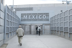 Border crossing. SAN YSIDRO, UNITED STATES - NOVEMBER 27, 2013: Pedestrians walk through the revolving metal gate from the U.S. to Mexico at the new Stock Photo