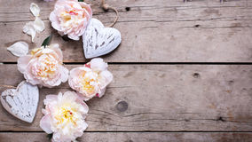 Border from decorative hearts and  pink peonies flowers on aged Stock Images