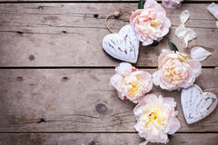 Border from decorative hearts and  pink peonies flowers on aged Stock Photography