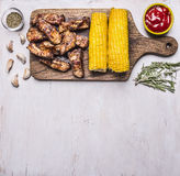 Border with delicious fried lamb ribs on a cutting board grilled with spicy sauce, herbs and corn with text area on white  wooden Royalty Free Stock Images