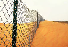 Border in a Desert. A long barrier border in a sandy desert Stock Image