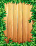 Border design with green leaves on wooden wall Royalty Free Stock Photo
