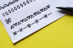 Border drawings. Drawings of seamless borders on paper with black brush on yellow background Royalty Free Stock Photos