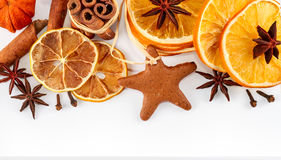 Border of dried oranges, lemons, mandarins, star anise, cinnamon sticks and gingerbread, isolated on white Royalty Free Stock Image