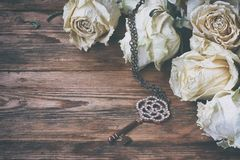 Border of dry white roses, key on chain Royalty Free Stock Image