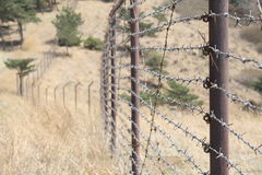 Border Fence. A wire fence in hilly scrubland topped with razor wire Stock Images