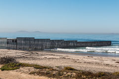 Border Fence Along the US-Mexico Border with Los Coronados. Border Field State Park beach with the international border fence between Tijuana, Mexico and San Stock Photo