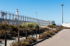 Border Fence with Lighthouse and Security Tower. Tijuana lighthouse on the Mexico side and a security tower with cameras and motion sensors on the San Diego side stock images