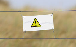 Border fence - Old plastic sign with a flag Royalty Free Stock Images