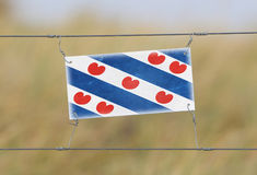 Border fence - Old plastic sign with a flag Royalty Free Stock Photos