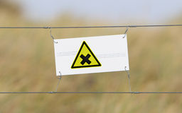 Border fence - Old plastic sign with a flag. Irritation Stock Image
