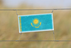 Border fence - Old plastic sign with a flag. Kazakhstan Royalty Free Stock Photos