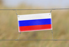 Border fence - Old plastic sign with a flag. Russia Stock Photos