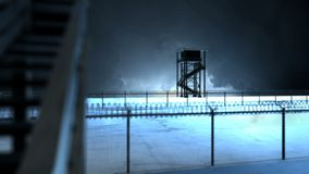 Border Fence with Two Watchtowers on a Stormy Night