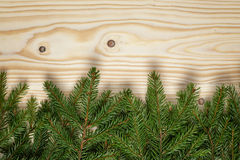 Border from fir twigs on wood background royalty free stock photo