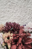 Border with flowers against white wall. Border with artificial flowers against white wall with copy space stock image