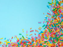 Border frame of colorful sprinkles on blue background royalty free stock photos