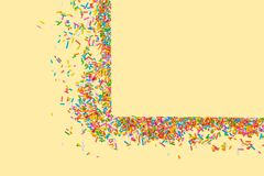 Border frame of colorful sprinkles on a yellow background with c royalty free stock images