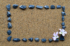 Border frame with gravel and pink flower. On the beach royalty free stock photo