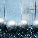 Border frame made of silver balls and tinsel on a blue wooden background. Christmas concept. Border frame made of silver balls and tinsel on a blue wooden Royalty Free Stock Images