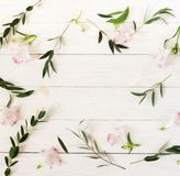 Border frame wreath made of pink flowers and eucalyptus branches. On white wooden background. holiday greeting card. Flat lay, top view. Flowers background stock images