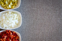 Border of fresh diced vegetables for cooking. Border composed of three bowls of fresh diced vegetables for cooking with zucchini or courgette, white onion and stock photos