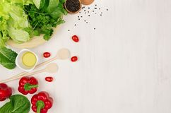 Border of fresh green greens, red paprika, cherry tomato, pepper, oil and utensils on soft white wooden background. Stock Image