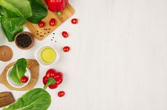 Border of fresh green greens, red paprika, cherry tomato, pepper, oil and utensils on soft white wooden background. Stock Photos