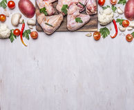 Border with Fresh raw chicken wings on a cutting board mushrooms and potatoes with parsley Hot red peppers cherry tomatoes  rust. Border with Fresh raw chicken Stock Photo