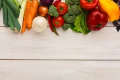 Border of fresh vegetables on wooden background with copy space. Border of fresh organic vegetables on white wood background. Healthy natural food on rustic Royalty Free Stock Image