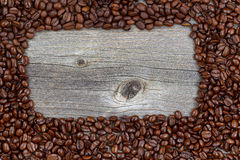 Border of freshly roasted coffee beans on aged wood Royalty Free Stock Photos
