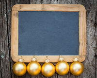 Border of gold Christmas balls. On vintage wooden blackboard blank Royalty Free Stock Photography