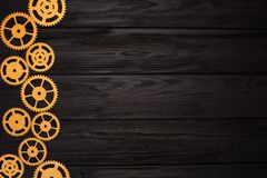 Border of gold gears on a black wooden background. View from above.  stock image
