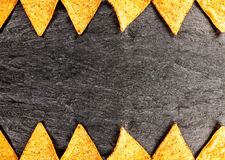 Border of golden crisp nachos. Or corn tortillas arrange top and bottom in a geometric pattern in horizontal format on textured slate with copyspace stock image