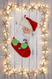 A border of golden star christmas lights, with a christmas stock. Ing and santa face hanging in the middle, on a destressed woodern background royalty free stock photo