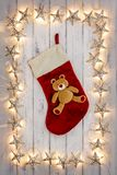 A border of golden star christmas lights, with a christmas stock. Ing and teddy hanging in the middle, on a destressed woodern background royalty free stock image