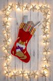 A border of golden star christmas lights, with a kittens christmas stocking and presents, on a destressed woodern background. A border of golden star christmas stock photo