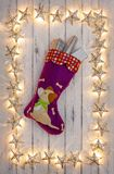 A border of golden star christmas lights, with a puppies christmas stocking and presents, on a destressed woodern background stock photo