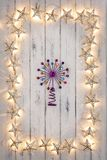 A border of golden star christmas lights, and a purple star, on. A border of golden star christmas lights, and a purple star in the middle, on a destressed royalty free stock photos