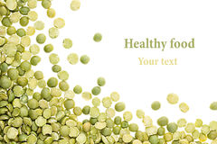 Border of green dry purified peas closeup with copy space on white background. Royalty Free Stock Images