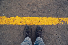 At the Border line. Male sneakers on the asphalt road with yellow line. Border line concept, danger or warning sign Royalty Free Stock Photography