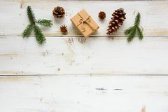 Preparing for holiday. Border made of Christmas gift, pine branches on white wooden background. Preparing for Christmas or New Year holiday. Flat lay, top view Royalty Free Stock Photos