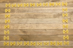 Border made of raw bow shape pasta. On wood Royalty Free Stock Photo