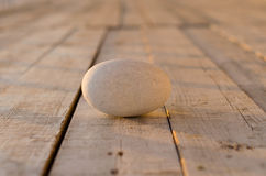 Border of natural white pebbles on the side over a textured painted white background of rough wooden boards Royalty Free Stock Images