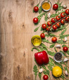 Border with oil, cherry tomatoes on a branch, pepper, seasoning, arugula, garlic border ,with text area on wooden rustic backgroun Stock Photo